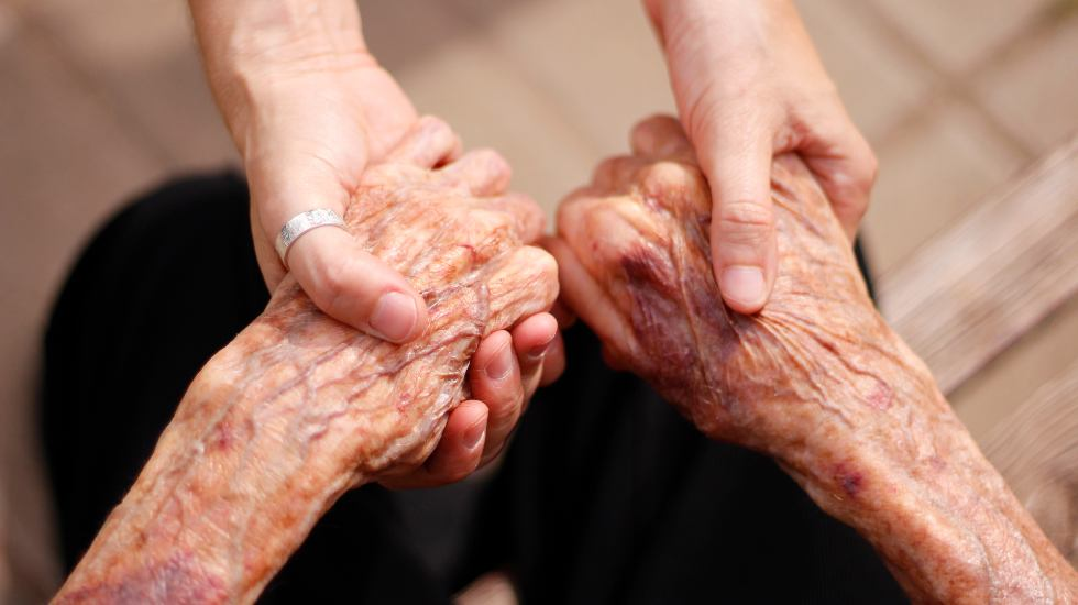 young woman holding hands of an elderly woman to support her