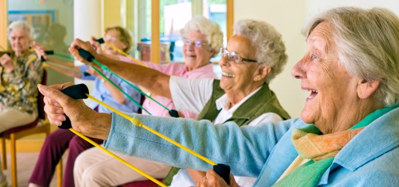 group of elderly woman smiling whilst exercising sitting down