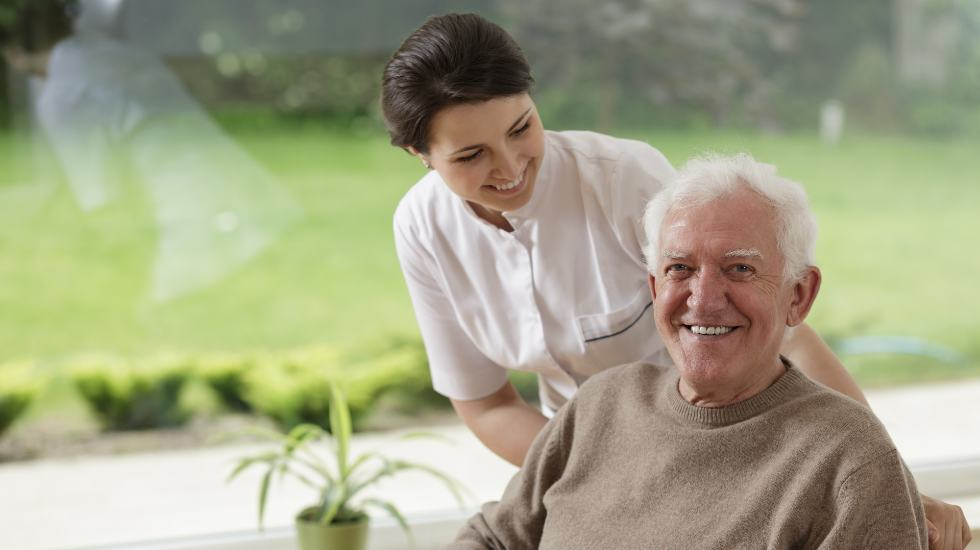 carer smiling and standing behind patient with their hands on the back of their wheelchair