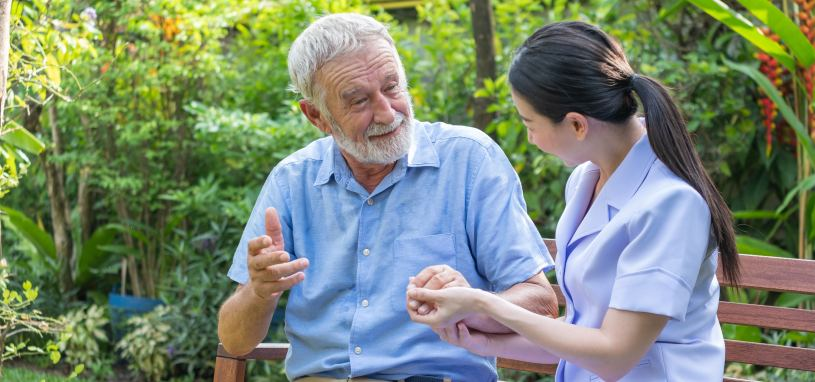 carer sitting beside elderly patient and holding his hand