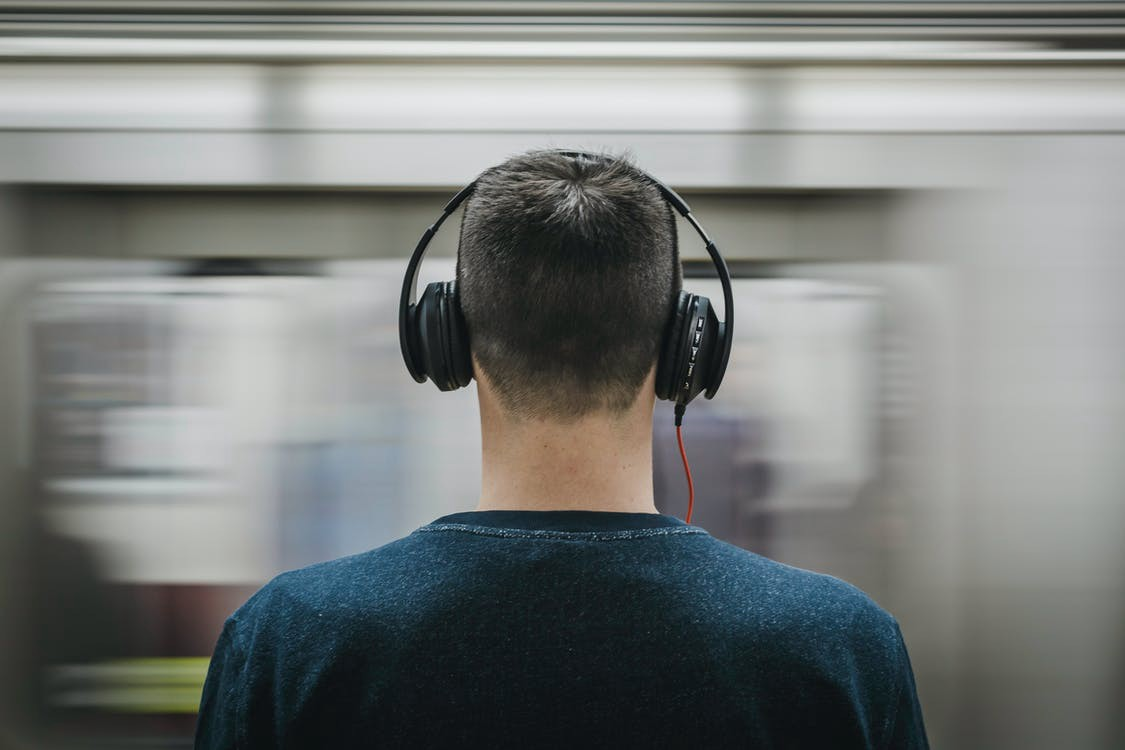 Man wearing headphones at a subway station
