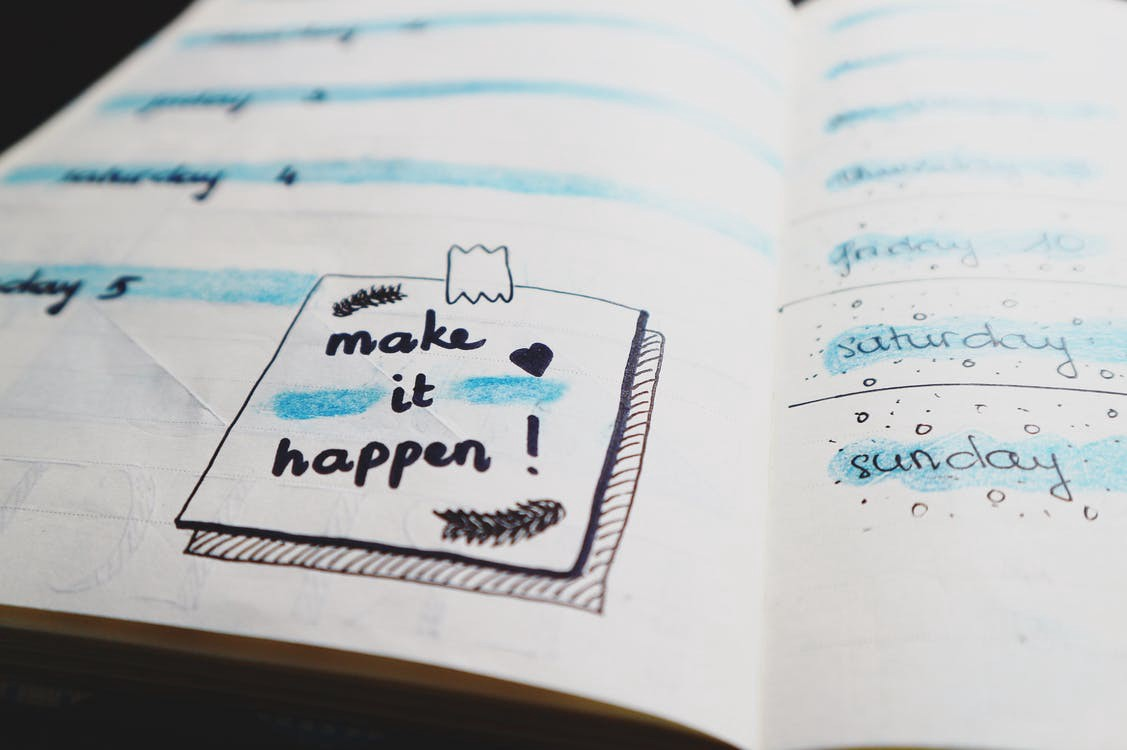 """make it happen"" written in a planner"