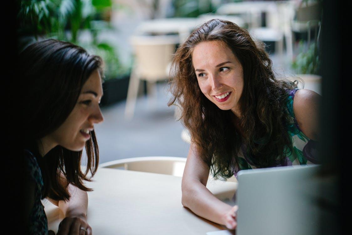 Two Talking Women While Using Laptop