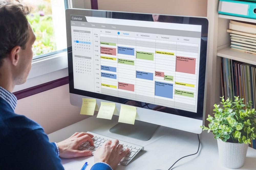 Man Scheduling Meetings on Calendar
