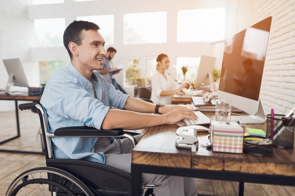 Man in Wheelchair Working Productively at Office