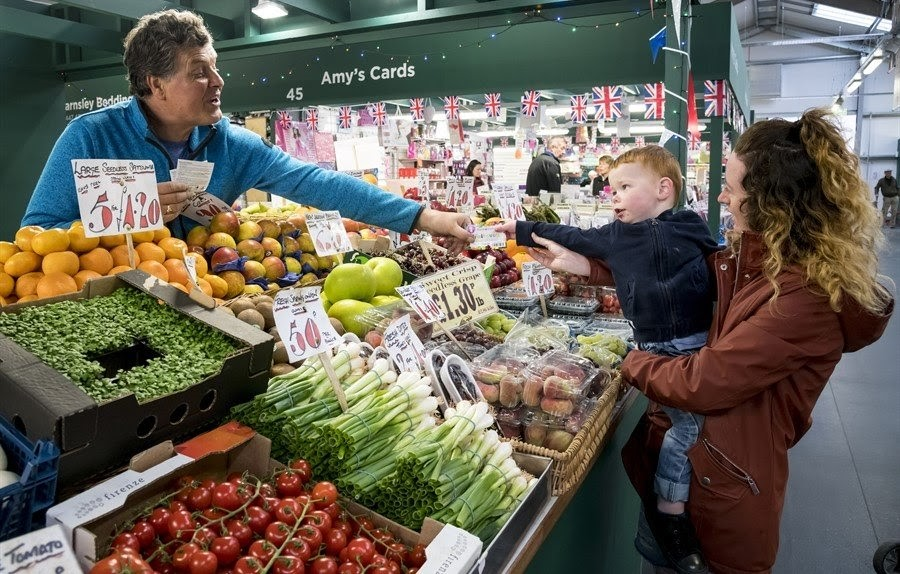 Woman and child at a fruit and veg stall