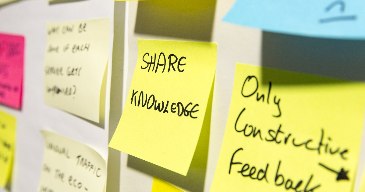 Board with post-it notes; prominent one has 'Share knowledge' written on it