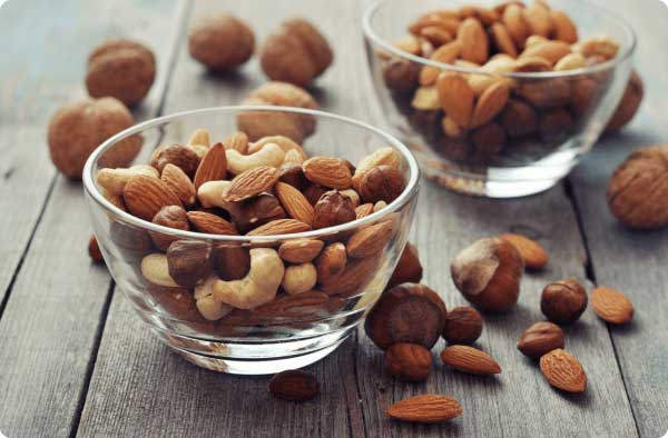 Mixed nuts in a glass bowl on a wooden table