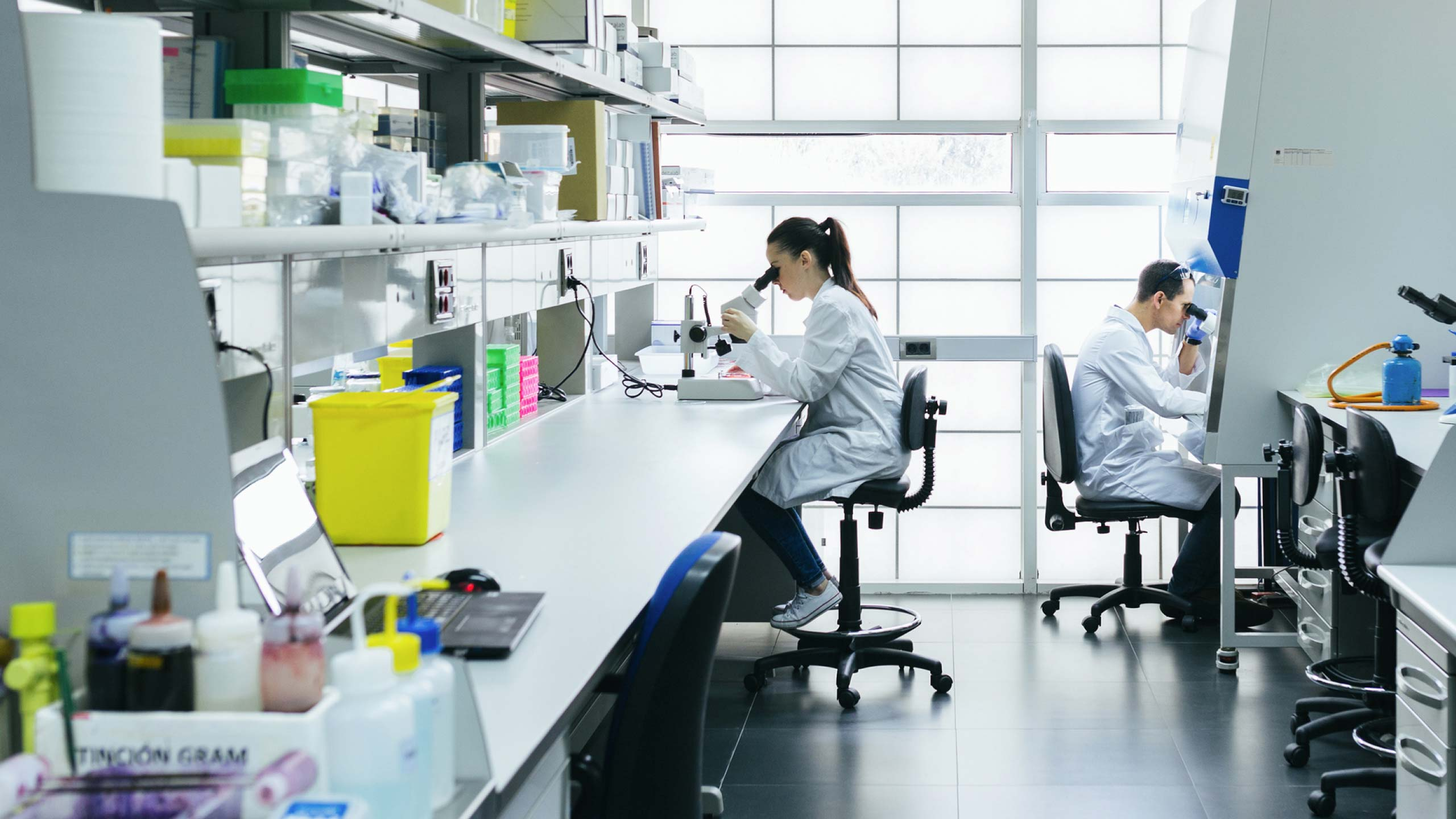 Two medical researchers in a lab looking at microscopes