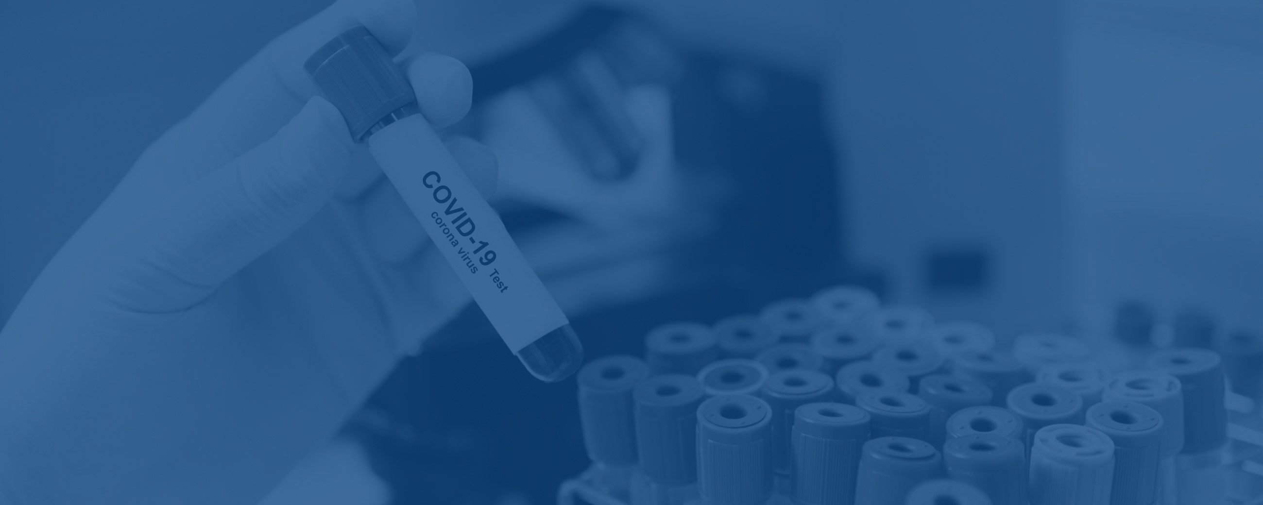 "Blue background image of a hand holding a test tube of blood labeled ""COVID-19 test"", with more blood vials in the background"