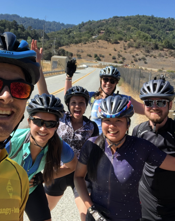 Six Virtans smiling and posing for a photo during a bicycle ride in California