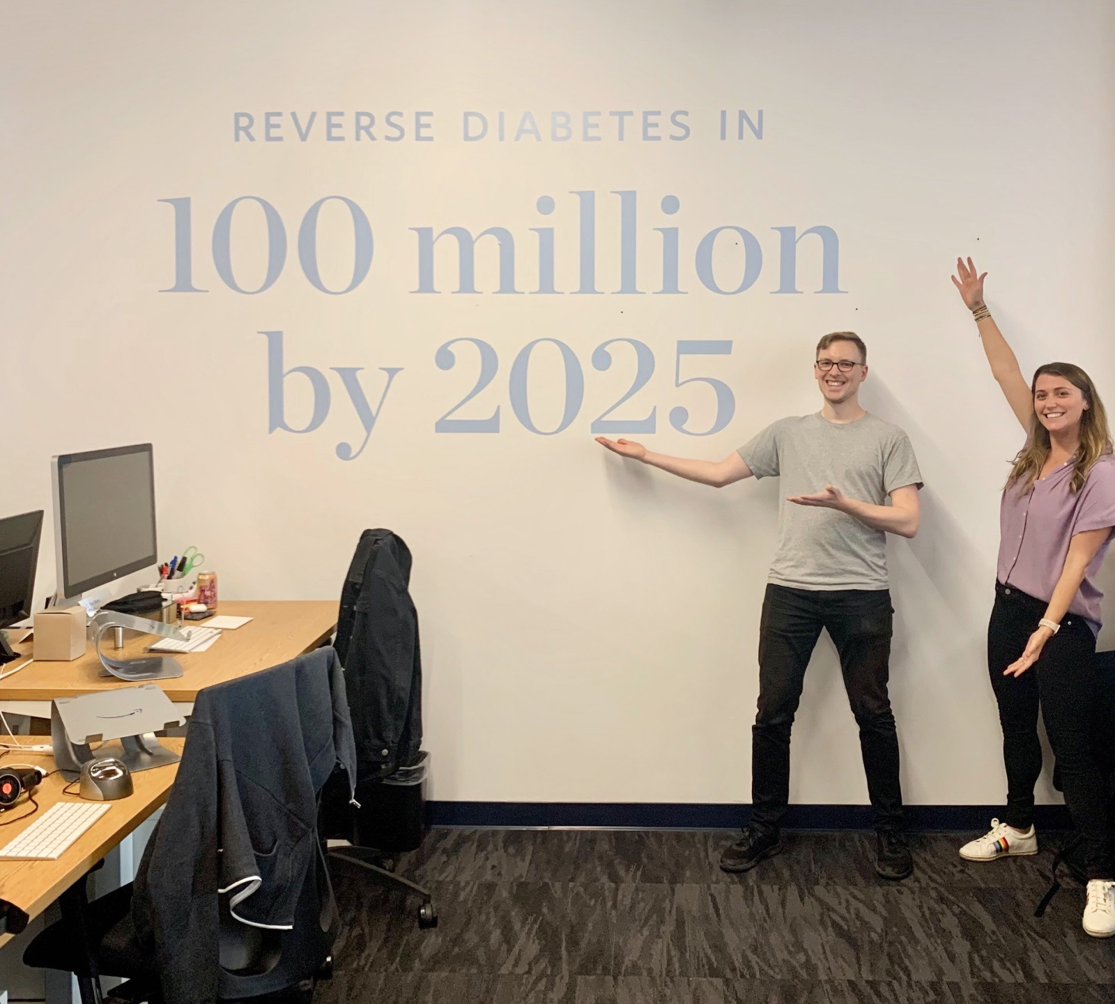 "Two Virtans standing next to Virta's mission statement, printed on the wall (""Reverse diabetes in 100 million by 2025"")"