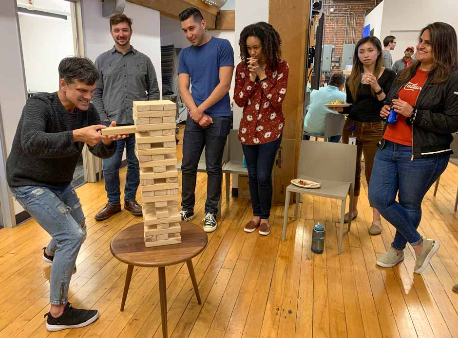 Six Virtans playing a game of Jenga during an office happy hour