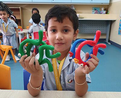 Cute GIIS Nursery Class boy learning with objects in Class