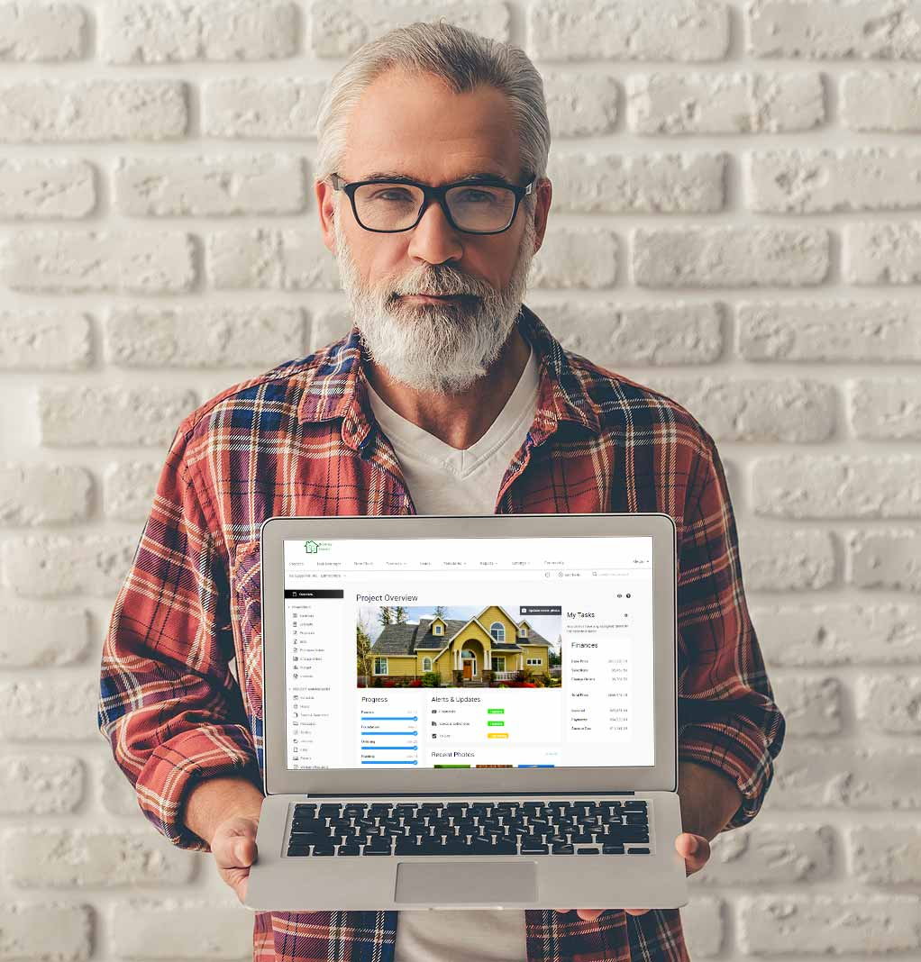 Builder holding laptop with CoConstruct app open