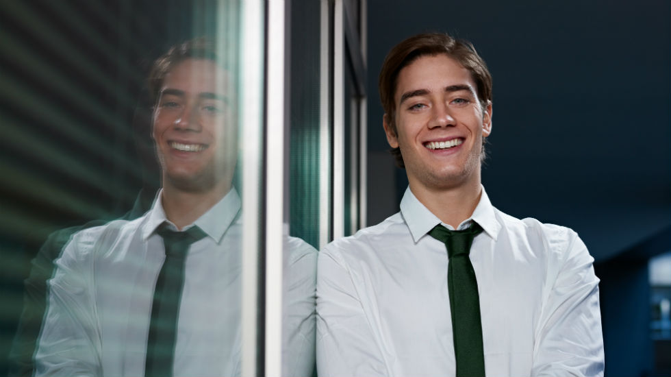 young man smiling beside window
