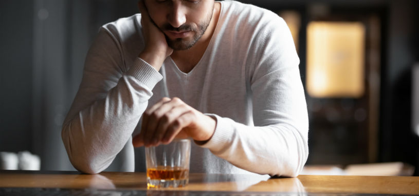 young man nurses a glass of whisky