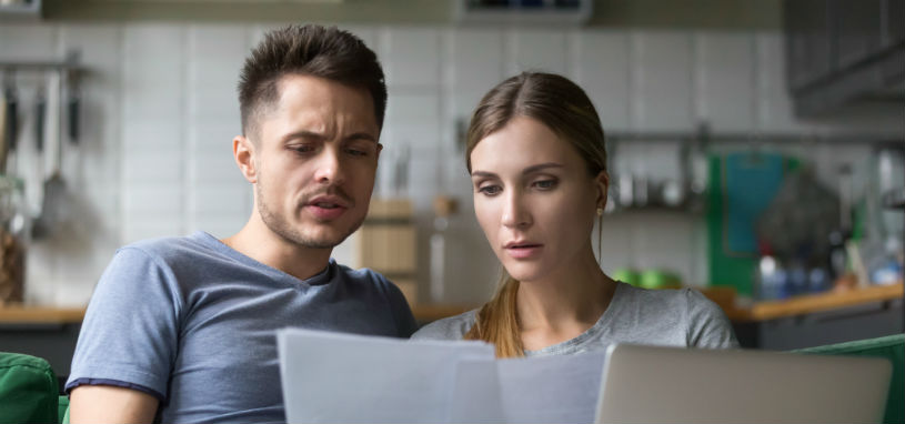 concerned couple looking at bills