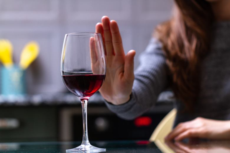 woman refusing a glass of wine