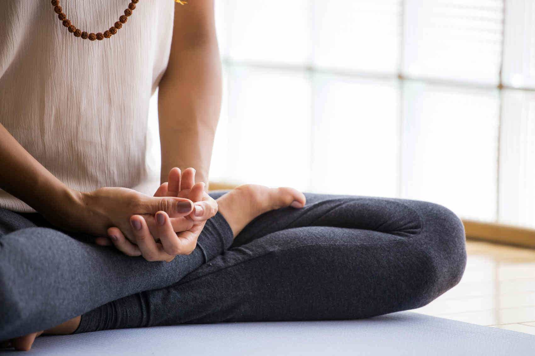 woman practicing meditation with legs crossed