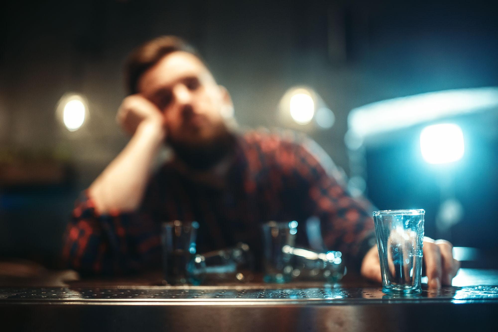 man with blurred vision drunk at bar