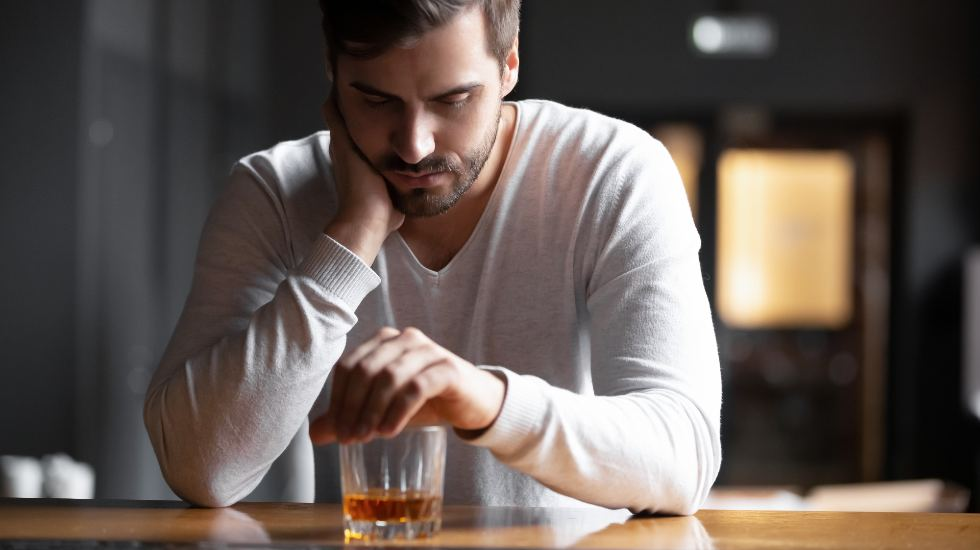 upset man sitting alone at a bar with a glass of whiskey in front of him
