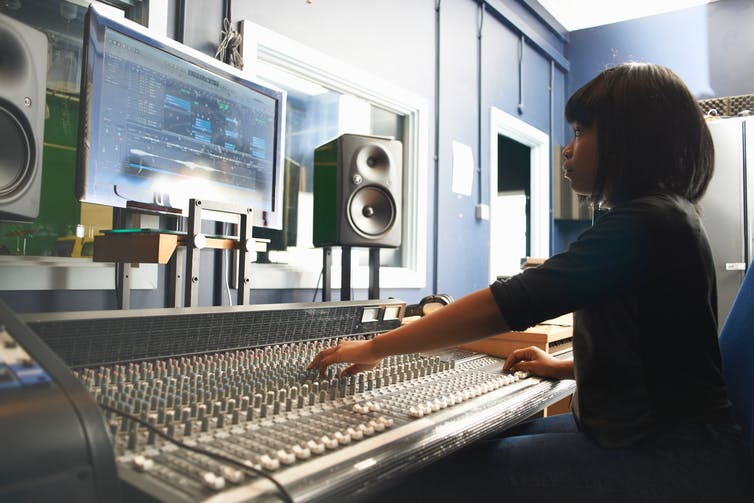 A young girl uses a soundboard.