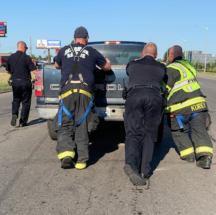 Firefighters and police offers move truck at crash scene