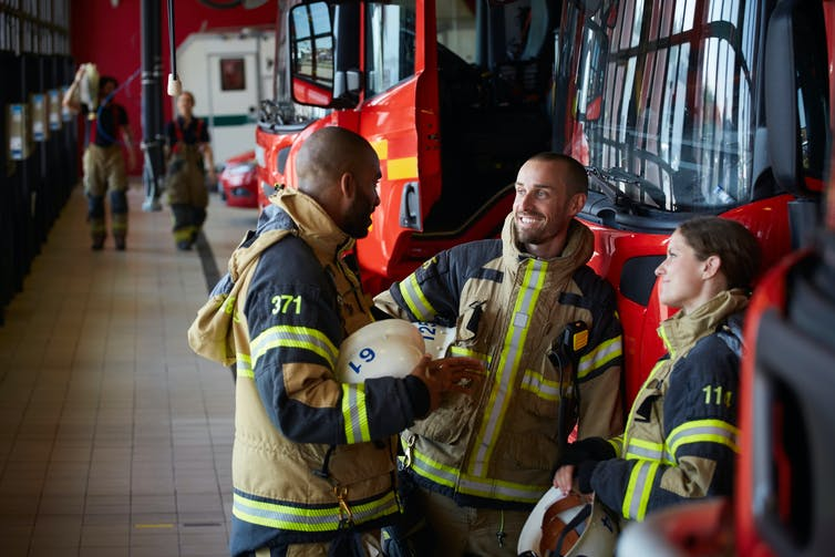 Firefighters dressed in uniforms, talking at fire station