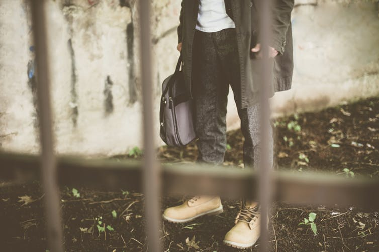 Man wearing working boots standing in front of jail bars with work bag