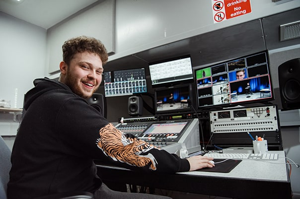 Man in front of video editing desk