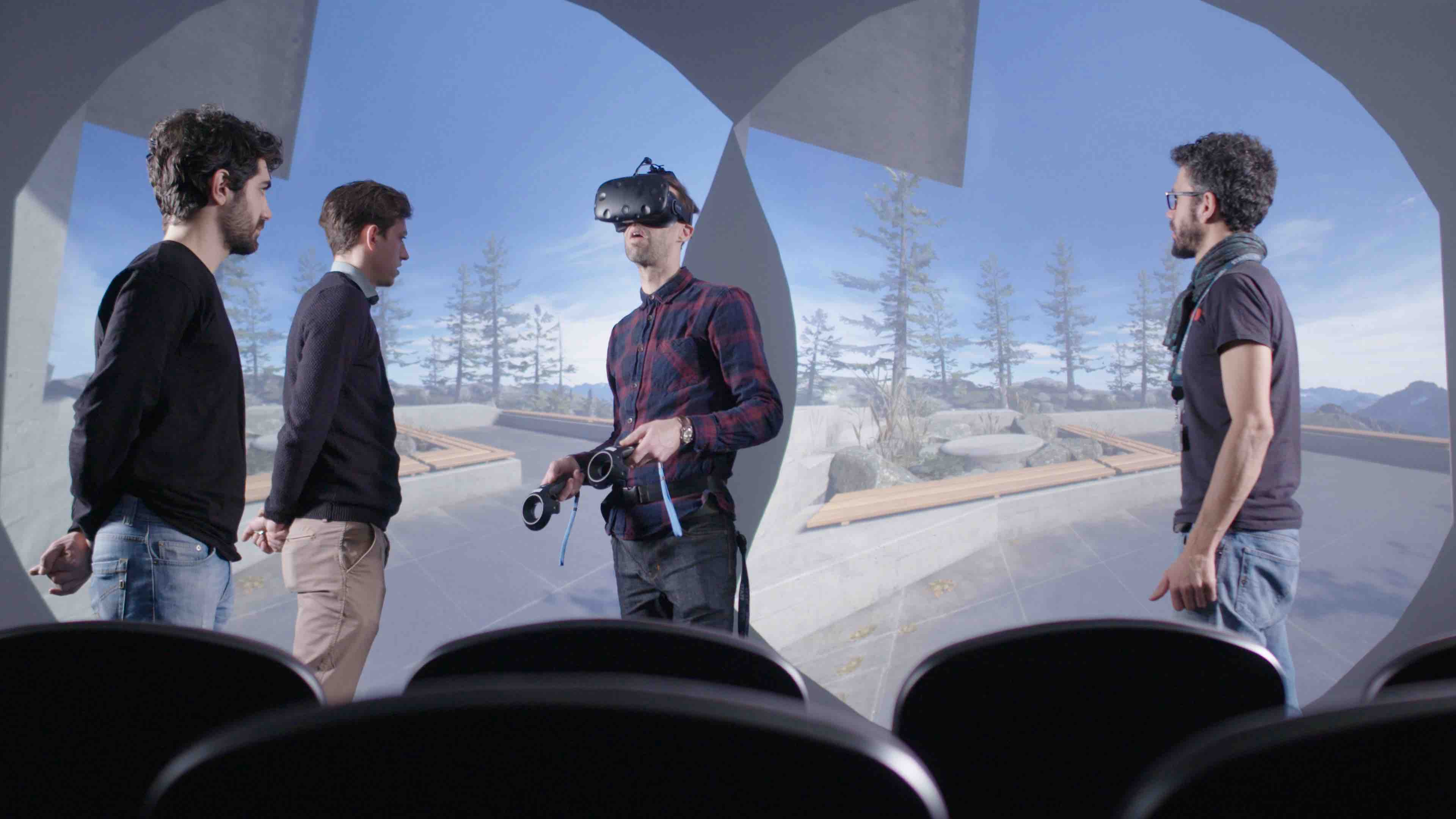 Man wearing VR headset in front of large screen