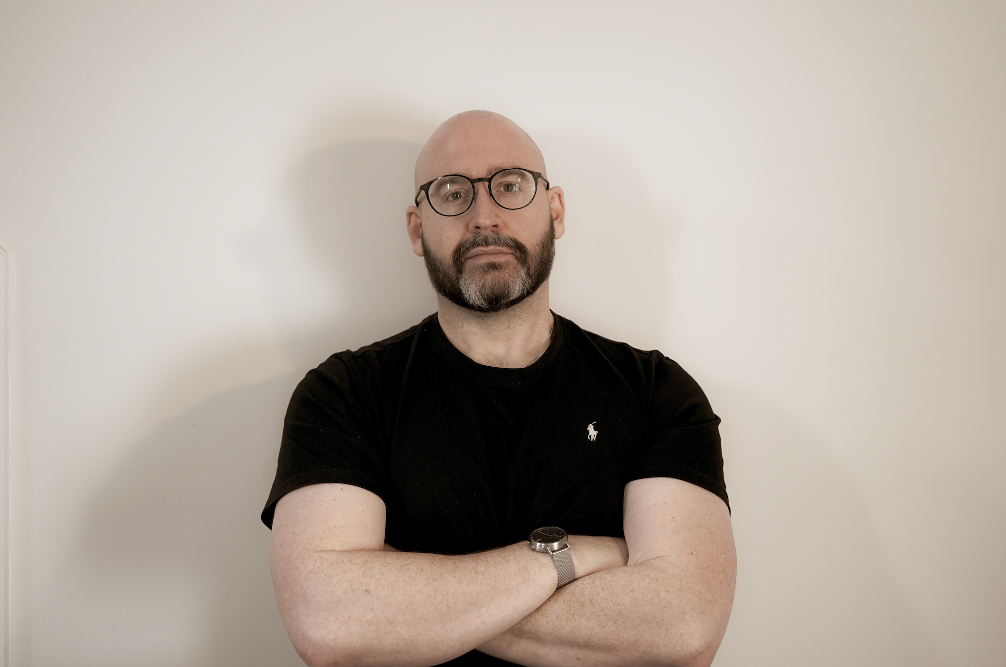 A bald white man with a short, neat beard and glasses looks into the camera. He is unsmiling and has his arms crossed. He wears a black shirt and is standing against a plain beige background.