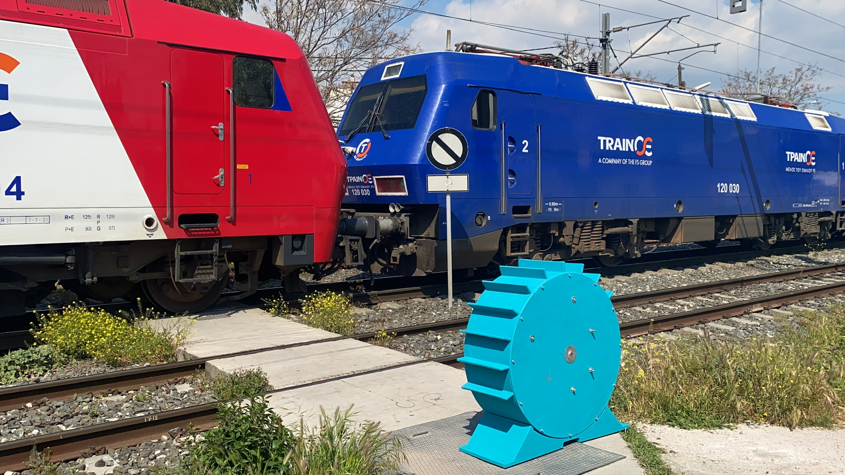 A render of a blue flywheel has been added to this photo of two trams..