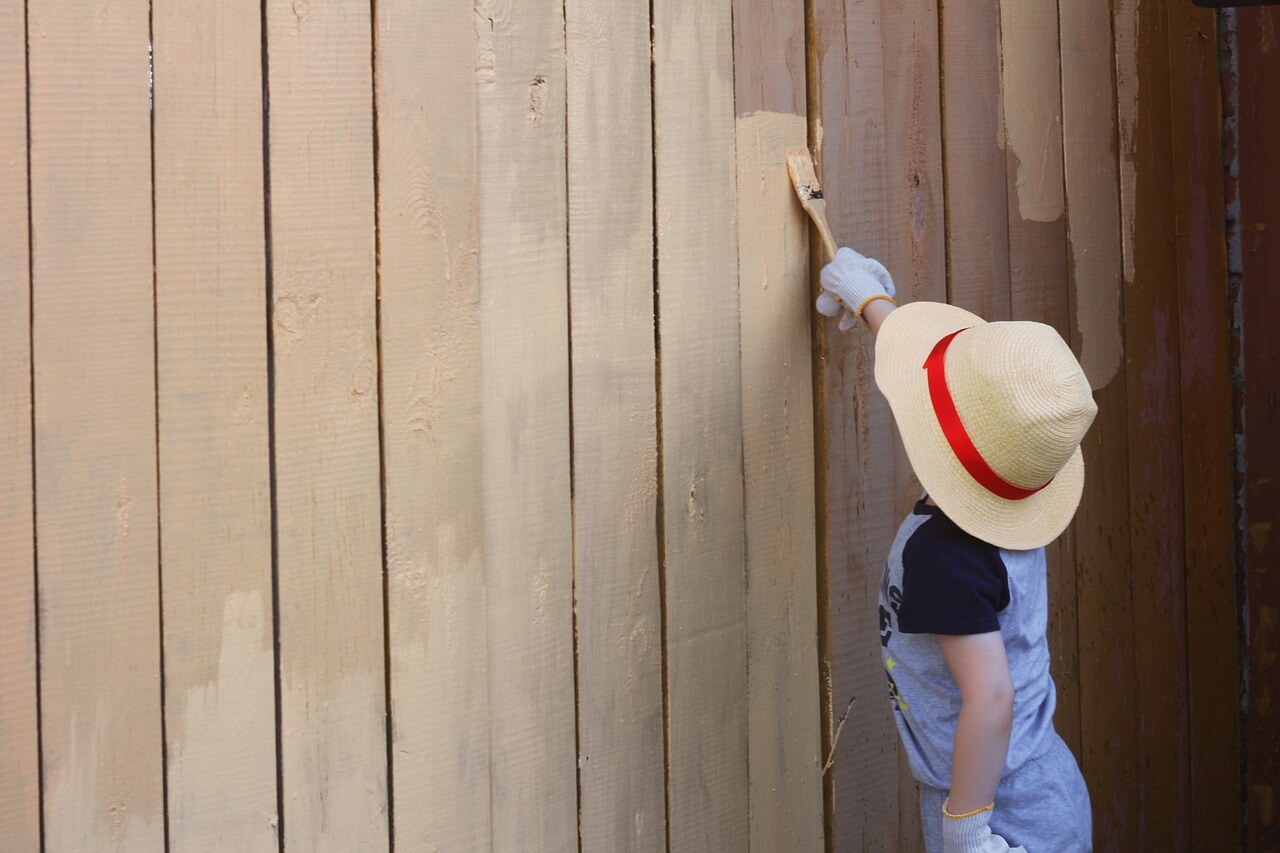 boy painting a fence