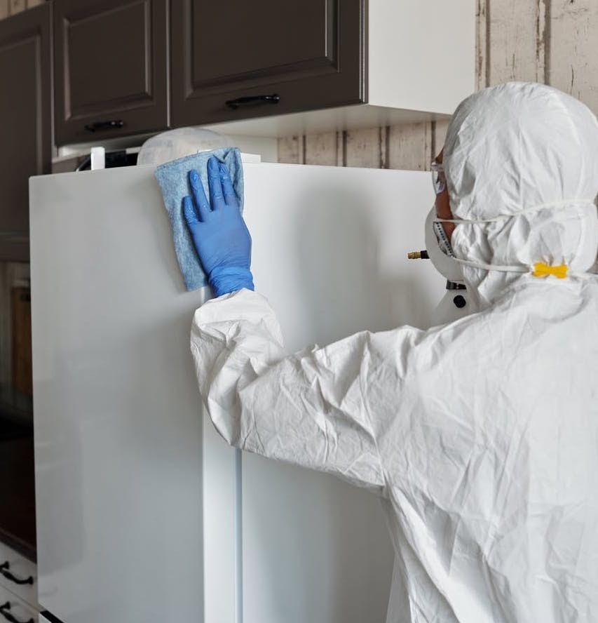 person scrubbing dirty fridge in building