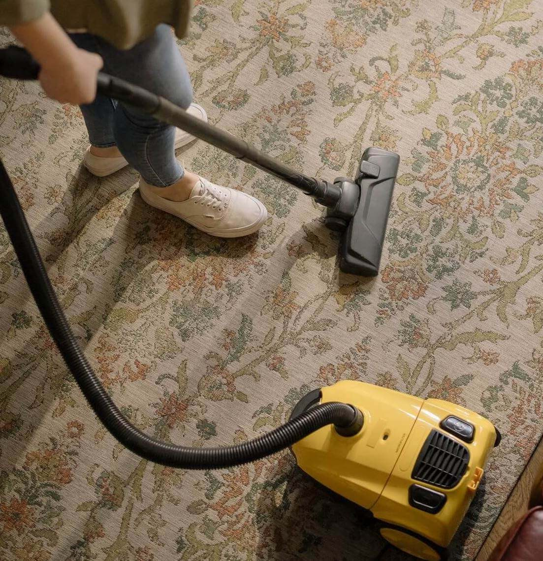 lady using a vacuum cleaner on carpets