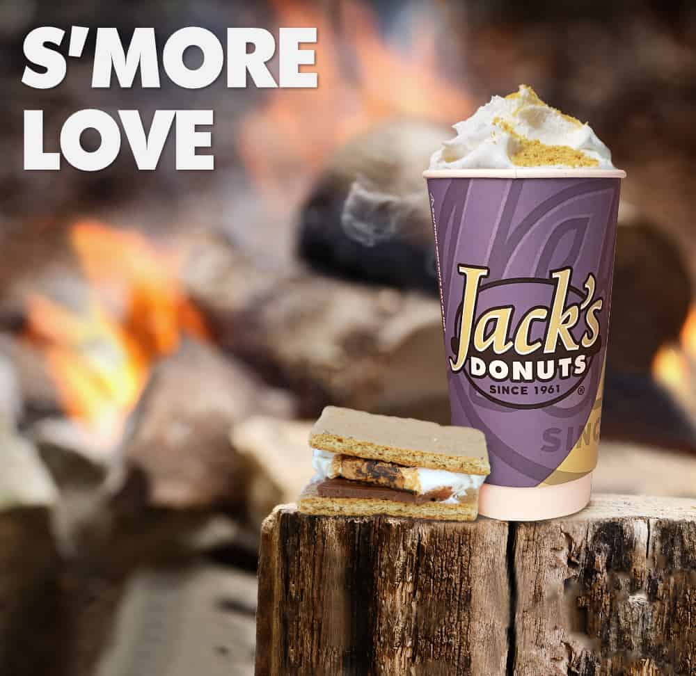 Cup of warm S'more Love Mocha sitting next to a fire with an actual s'more.