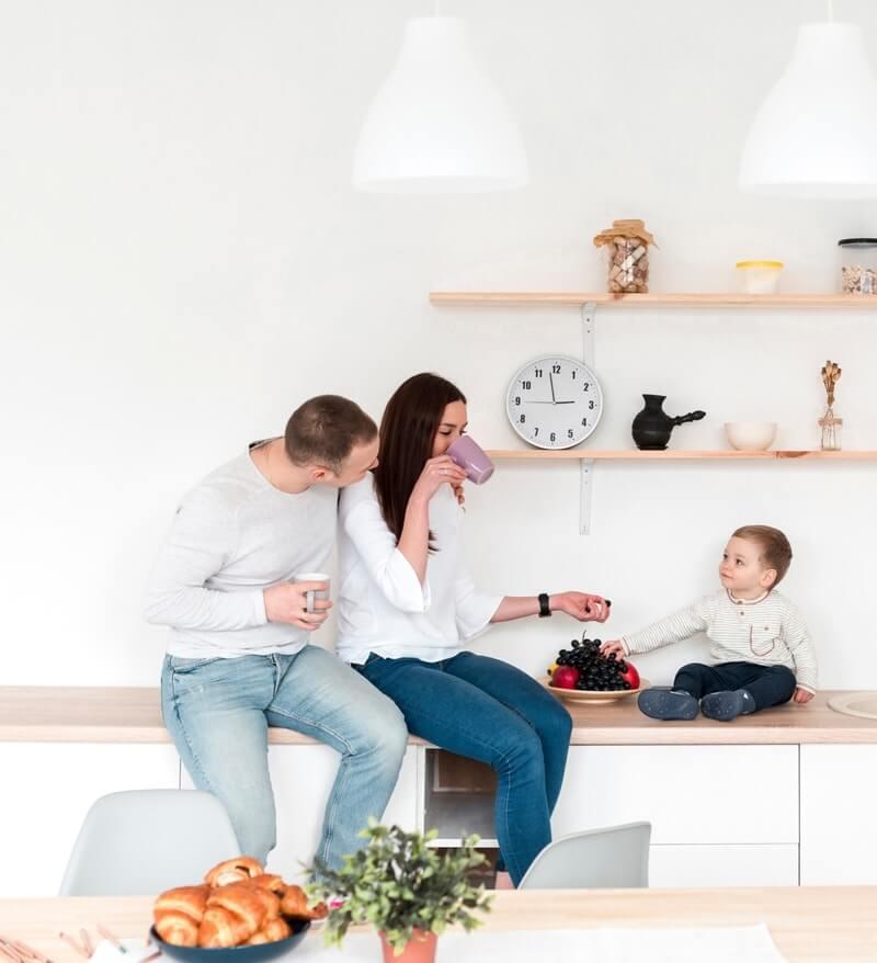 Glad familie i køkkenet og spiser frugt