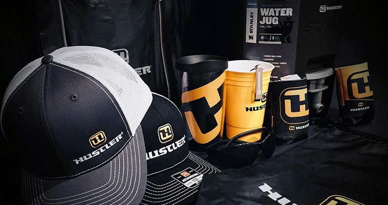 A collection of black and yellow Hustler branded hats, cups, koozies and bags.