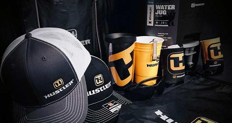 Una colección de sombreros, tazas, koozies y bolsas negras y amarillas de la marca Hustler.