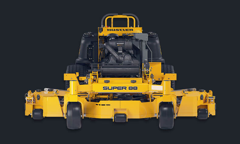 A straight on view of a yellow stand-on Hustler mower with deck wings on a black background.