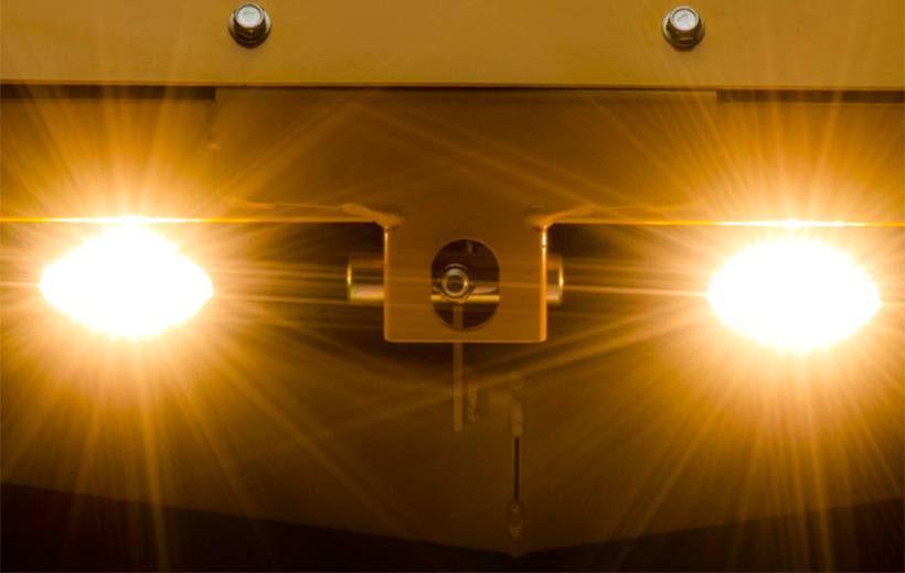 Image of lights mounted on the front of a yellow mower