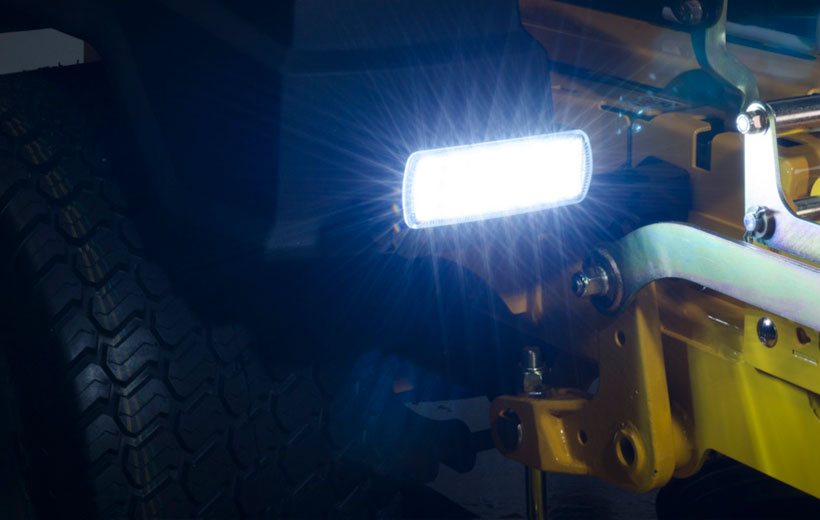 Image of a rectangular light lit up mounted in front of the drive wheel of a mower