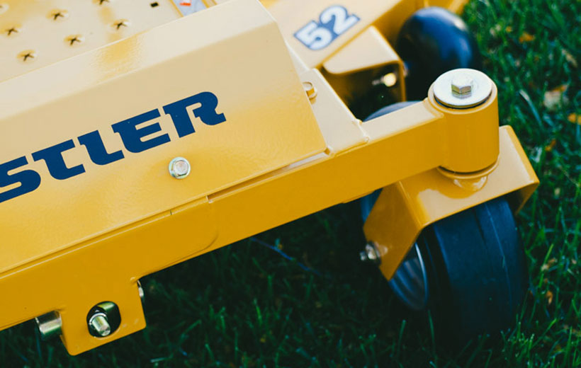 Image of a yellow riding mower front frame and one tire