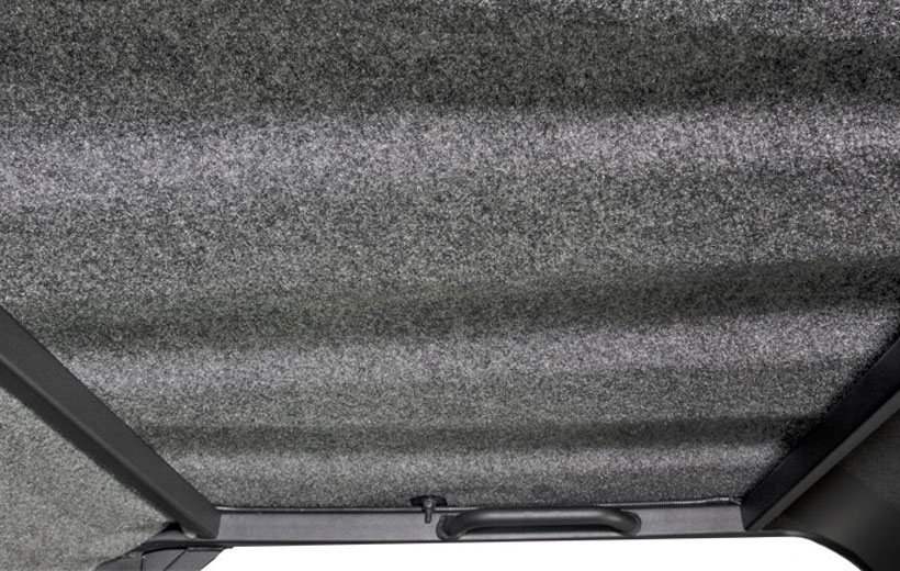 Image of the inside of a utility vehicle roof with gray material on it.
