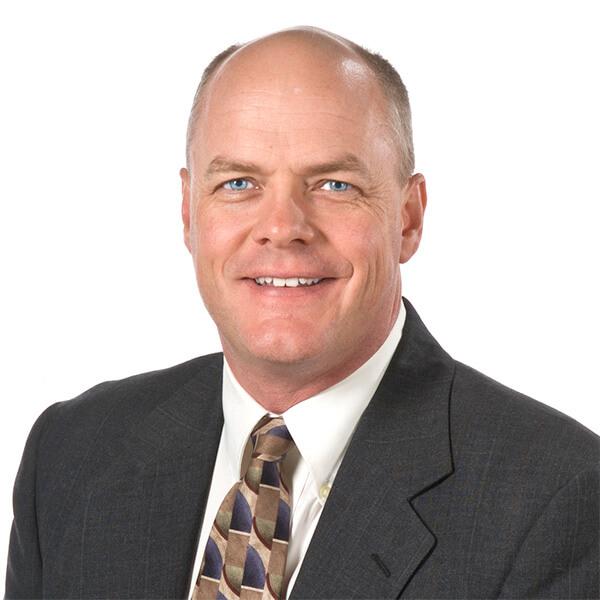 imagen de la cabeza y los hombros de un hombre blanco con traje negro y corbata dorada