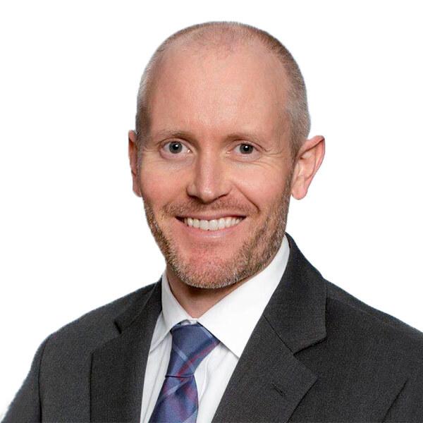 imagen de la cabeza y los hombros de un hombre blanco con traje negro y corbata azul