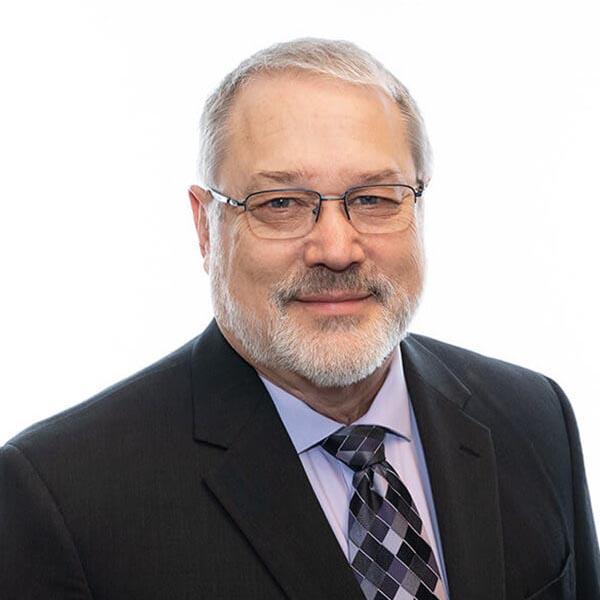 Imagen de la cabeza y los hombros de un hombre blanco con traje negro y corbata púrpura