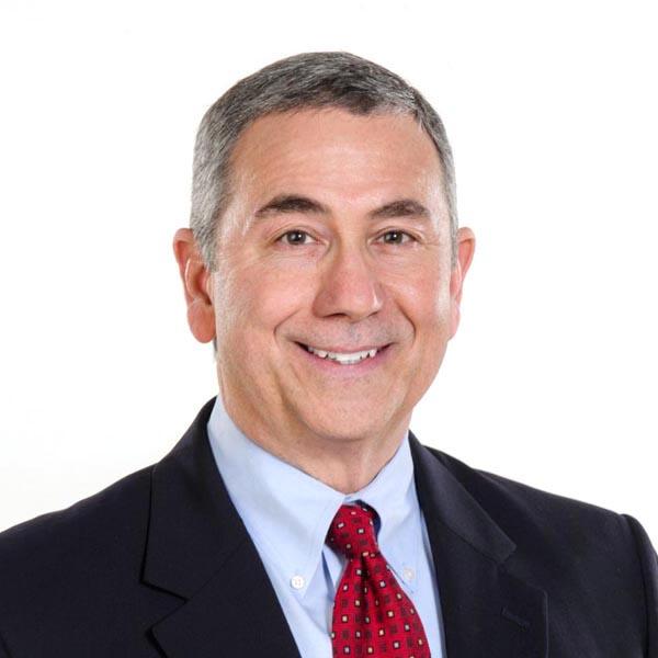 imagen de la cabeza y los hombros de un hombre blanco con traje y corbata roja